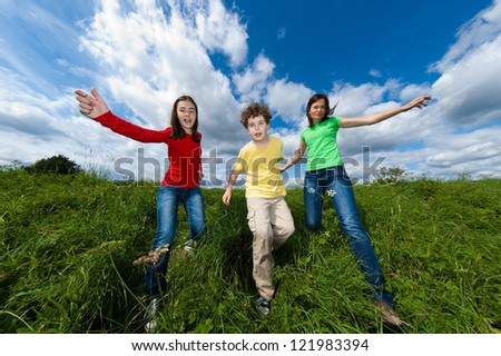 Mother with kids running, jumping outdoor