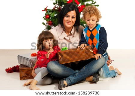 Mother with kids sitting near Christmas tree and holding present - stock photo
