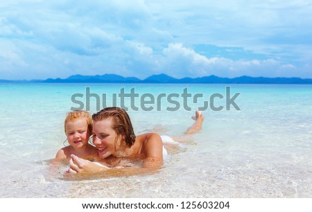 Mother with little baby girl on summer beach - stock photo