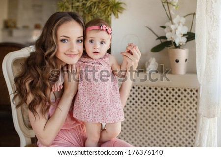 Mother with little baby in home interior young beautiful mom hugging daughter, pretty brunet woman playing with cute small girl, smiling girl holding adorable sweet child, happy family concept