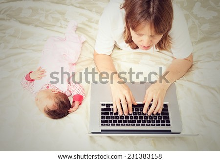 mother with little baby working from home - stock photo