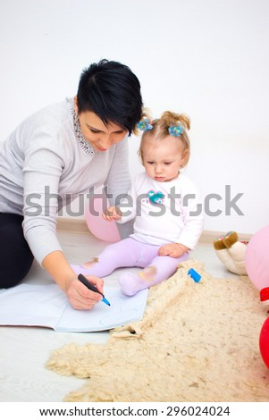 Mother with little baby, young beautiful mom with doter, pretty brunet woman playing with cute small girl, smiling girl holding adorable sweet child, happy family concept - stock photo