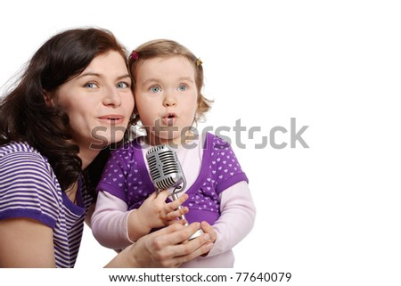 Mother with little daughter cheek to cheek sing into microphone. - stock photo
