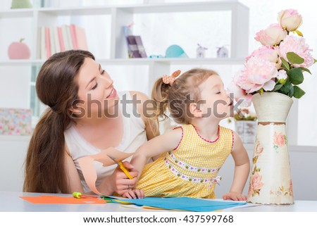 mother with little daughter in a yellow dress fun cut scissors colored paper. child smelling peonies - stock photo
