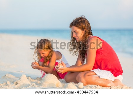 Mother with little daughter playing on the beach - stock photo