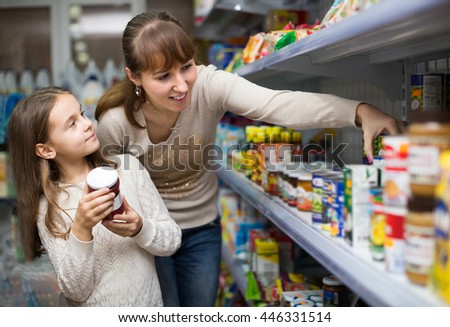 mother with little girl buying tinned food at grocery