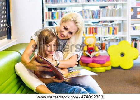 Mother with little girl read book together. Happy family, preschool concept. Parent educating children.