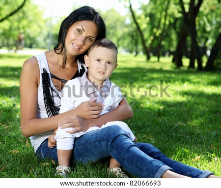 Mother with little son in the park on the grass