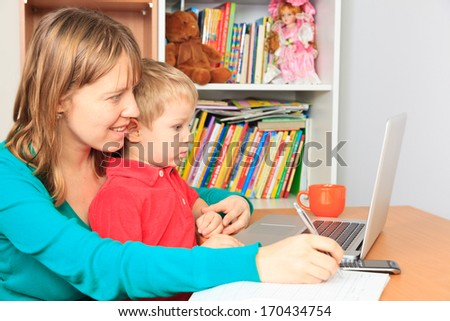mother with little son working on laptop at home - stock photo