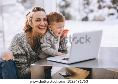 Mother with little son working on the computer at home