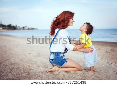 Mother with long curly red hair playing with her son on the beach. Happy family enjoying relaxing and enjoying life in nature. Outdoor shot. Copyspace - stock photo