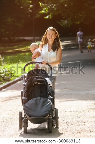 mother with newborn baby in arms during walking in garden
