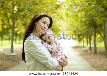 Mother with Resting Baby Girl at the Park - stock photo