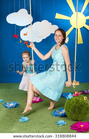 Mother with small daughter on the swing on the blue background with sun and clouds - stock photo