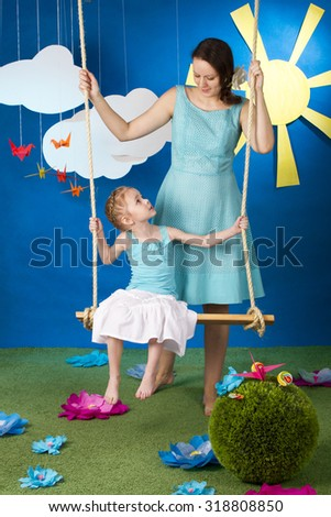 Mother with small daughter on the swing on the blue background with sun and clouds