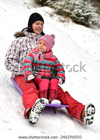 Mother with small girl going down in bobsleigh - stock photo