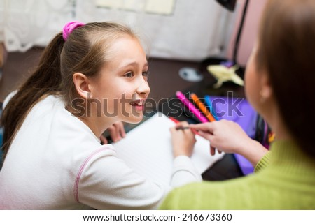 Mother with smiling little daughter doing homework in home interior - stock photo