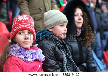 Mother with son and daughter in warm clothing sitting on stadium, focus on girl