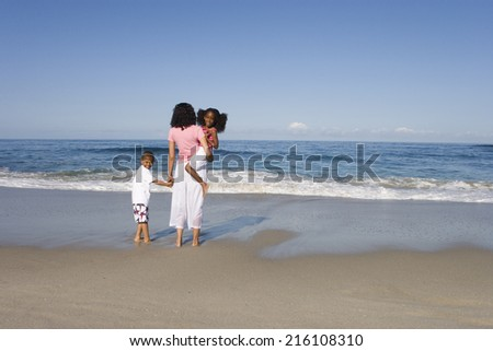 Mother with son and daughter (4-8) on beach