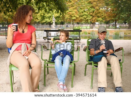 Mother with son and daughter sitting on a chair with a coffee and ice cream in the park - stock photo