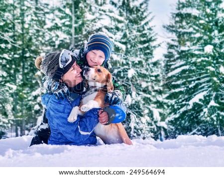 Mother with son and dog playing together in snow forest - stock photo
