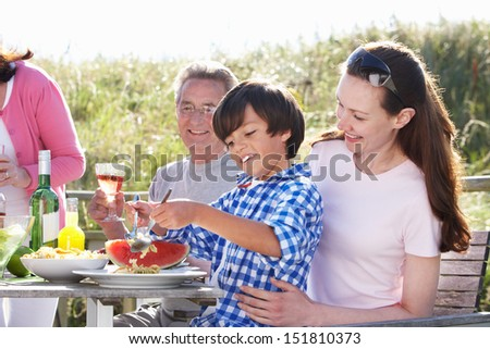 Mother With Son And Grandfather Enjoying Outdoor Barbeque