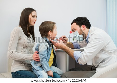 Mother with son during medical appointment, horizontal