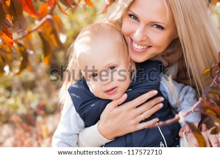Mother with son in autumn peach garden - stock photo