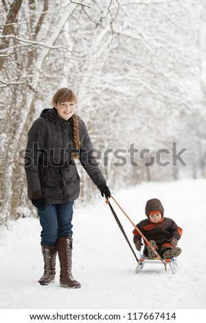 mother with son in winter park with sled - stock photo