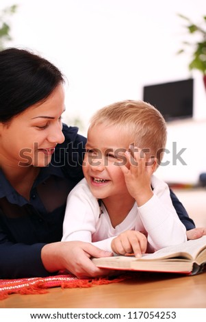 mother with son reading a book on a floor at home