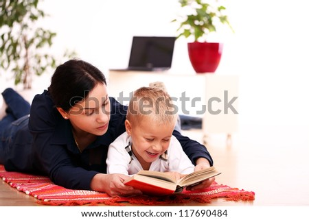 mother with son reading a book on a floor at home - stock photo