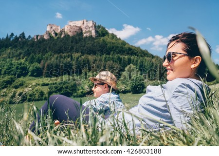 Mother with son rest together on green medow with view on old castle - stock photo