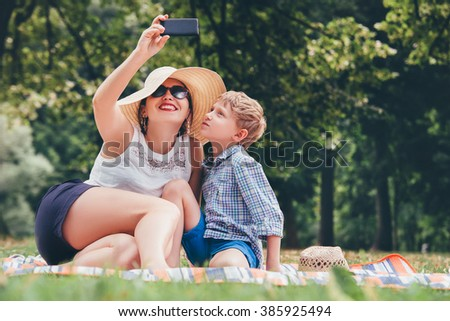 Mother with son take a selfie photo in summer park - stock photo