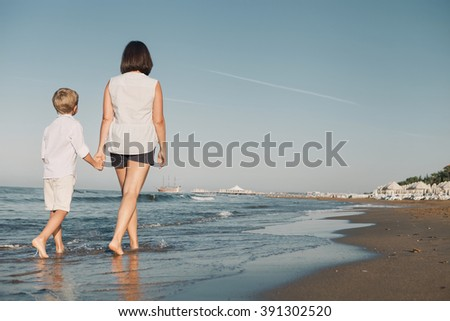 Mother with son walk together on surf sea line
