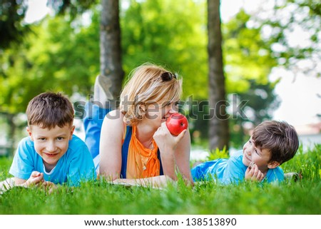 Mother with sons and apple at outdoor, teeth smile, happy family - stock photo