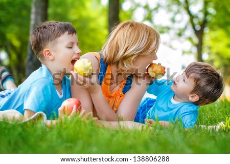 Mother with sons eating apple, healthy family - stock photo