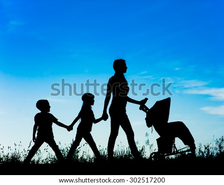 Mother with stroller and children walking at sunset