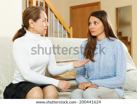 mother with  teen daughter having serious talking in living room