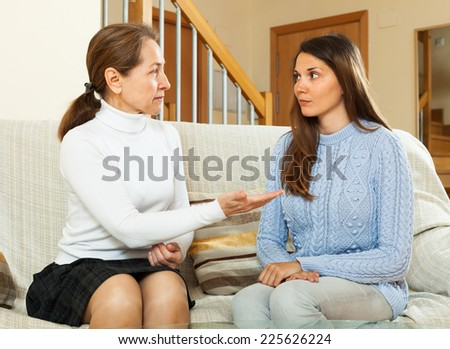 mother with  teen  having serious talking in living room