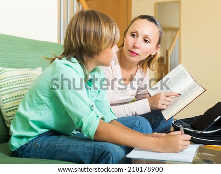Mother with teenager son doing homework together at home
