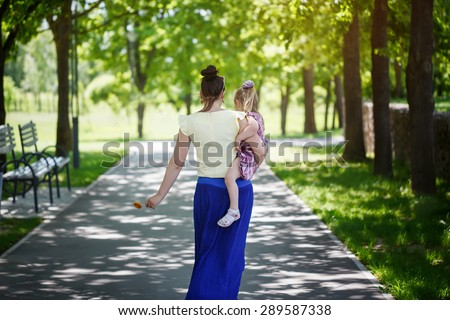 Mother with the daughter on hands walk in summer  park in sunny day. Rear view - stock photo