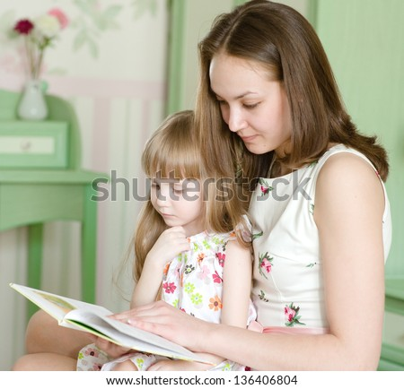 mother with the daughter read the book - stock photo