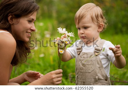 Mother with the son and a bouquet of chamomiles - stock photo