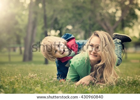 mother with the son on a grass in park play and have fun - stock photo