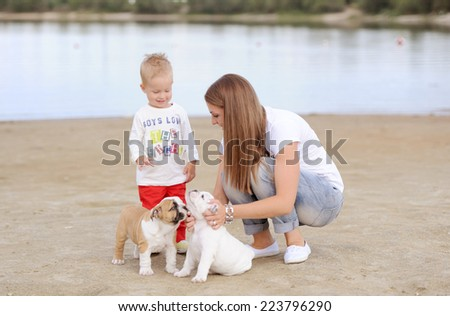 mother with the son play with puppies on the river bank - stock photo