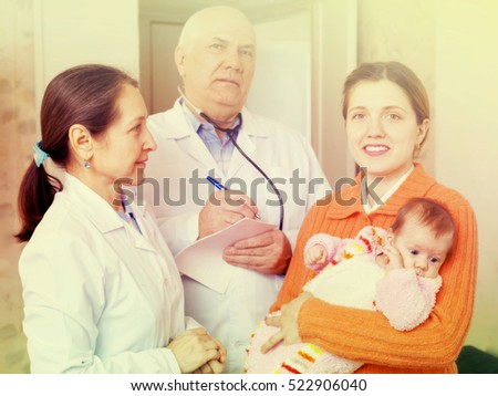 mother with three months baby in arms and pediatrician doctors in background