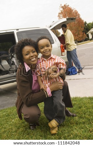 Mother with toddler with father in the background - stock photo