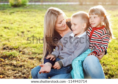 Mother with two children on the grass - stock photo