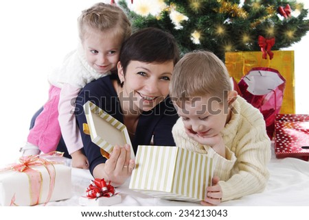 Mother with two children opening Christmas presents