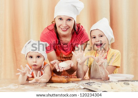 Mother with two daughters, all of the flour with the dough. - stock photo
